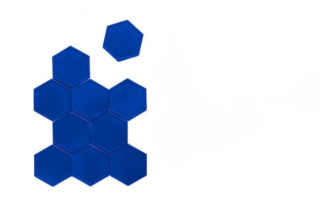 Les hexagones bleus forment une ruche sur blanc. un hexagone est séparé de la figure.