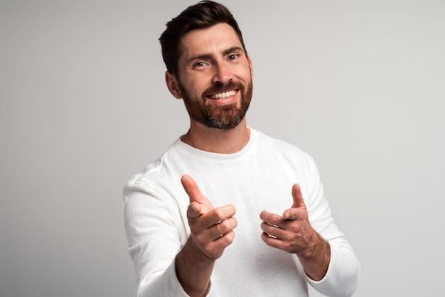 Hey vous. portrait d'un homme barbu heureux en chemise blanche souriant et pointant vers la caméra sur fond gris clair. prise de vue en studio