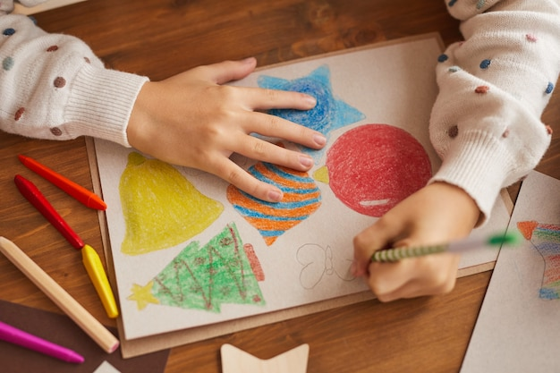 High angle close up of little girl dessin cartes de noël et décorations à l'école, espace copie