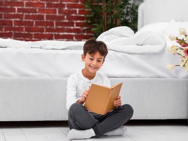 High angle, garçon, lecture plancher
