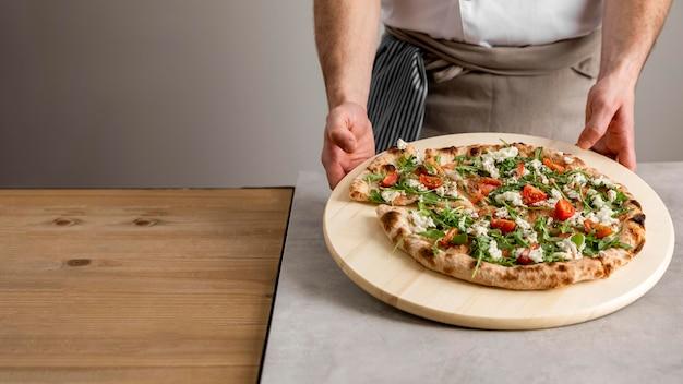 High angle man holding planche à découper avec pizza fraîche