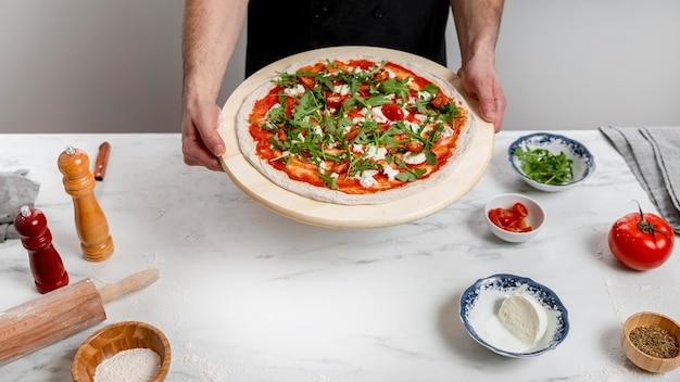 High angle man holding planche à découper avec pizza