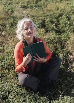 High angle old woman with book outdoors