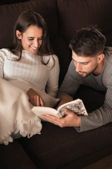 High angle petit ami en train de lire pour sa petite amie