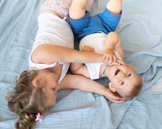 High angle petits enfants assis dans le lit
