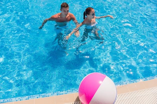 High angle view of young couple standing chest deep in resort piscine avec ballon de plage à rayures sur la terrasse de la piscine