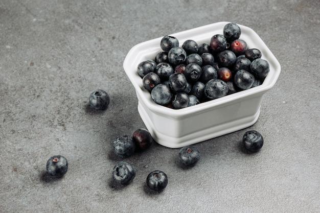 High angle view olives noires dans un bol carré sur fond gris. horizontal