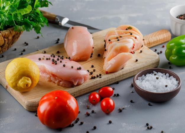 High angle view poitrines de poulet sur une planche à découper avec du citron, des tomates, du sel sur une surface grise