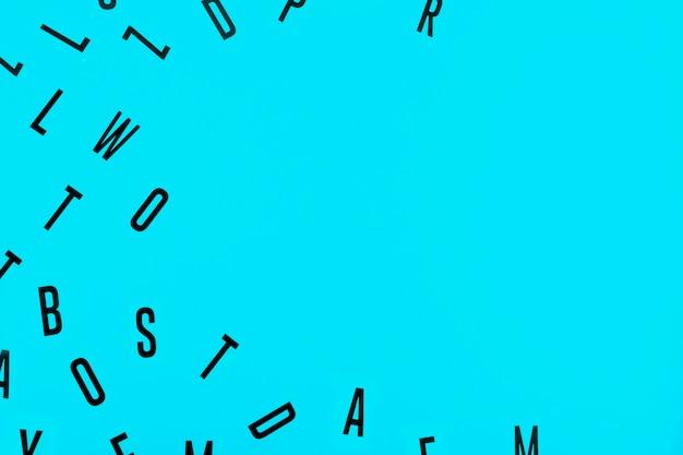 High angle de vue de différents alphabets noirs sur fond bleu
