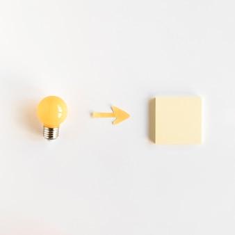 High angle de vue du symbole de la flèche entre l'ampoule et la note adhésive