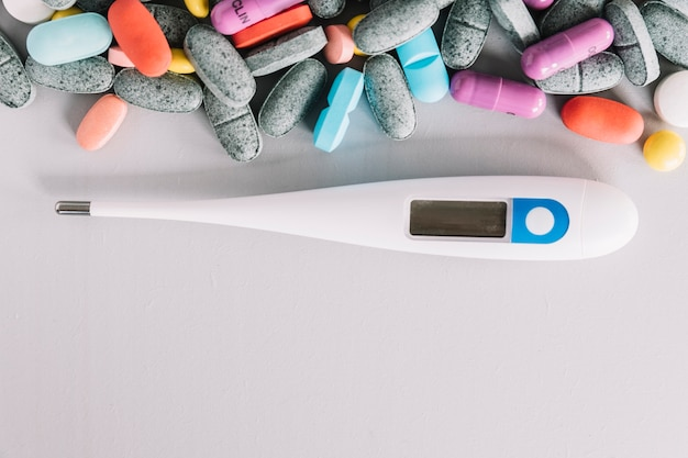 High angle de vue du thermomètre et des pilules colorées sur fond blanc