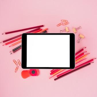 High angle de vue de table numérique sur les accessoires d'artisanat sur fond rose