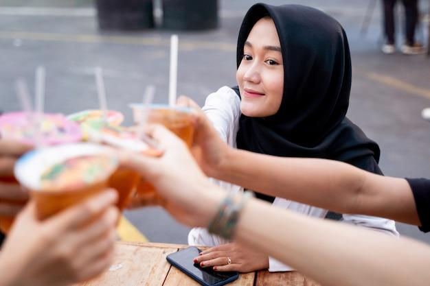 Hijab femme acclamant des boissons avec des amis