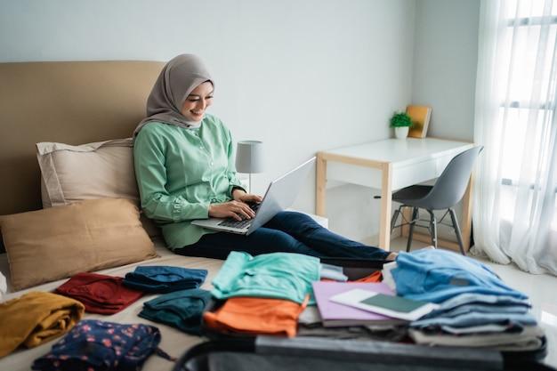 Hijab femme utilisant un ordinateur portable avec valise pleine