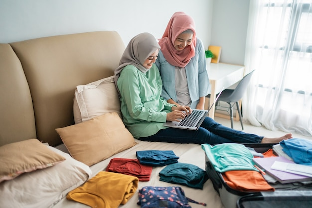 Hijab femmes utilisant un ordinateur portable avec une valise pleine