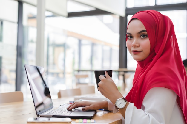Hijab rouge attrayant comptable musulman asiatique travaillant avec un ordinateur portable et tenant une tasse de café en co-working ou café-restaurant. gens d'affaires travaillant dans le concept de co-working.