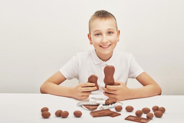 Ð¡hild boy avec des lapins au chocolat et des œufs pour pâques. oeufs en chocolat, lapins et tuiles. bonbons au chocolat pour les enfants