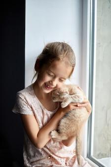 Ð¡hild girl joue avec un petit chaton ludique britannique à la maison windowsil