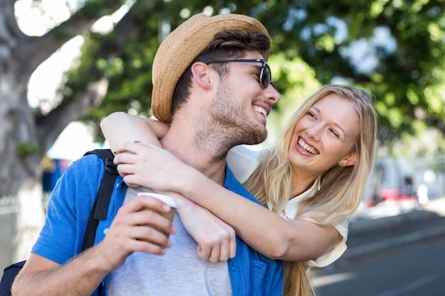 Hip couple embrassant et riant dans la ville