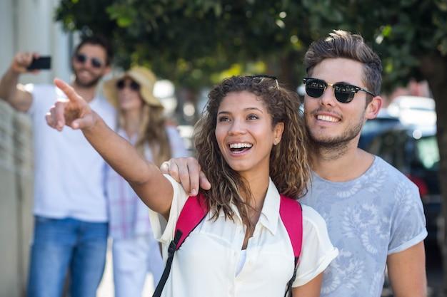 Hip couple pointant quelque part dans la ville