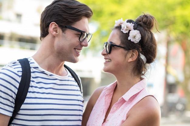 Hip couple souriant l'un à l'autre dans la ville