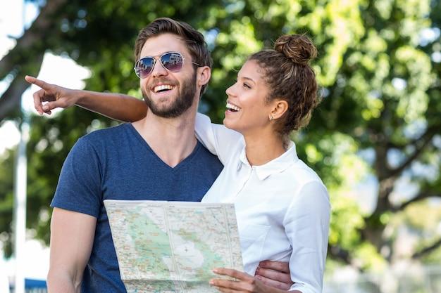 Hip couple vérifiant la carte et pointant quelque part dans la ville