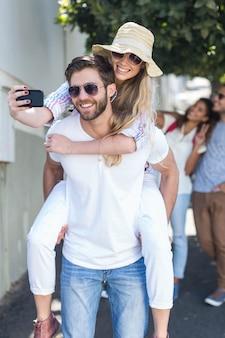 Hip man redonnant son cochon à sa petite amie et prenant selfie dans la rue