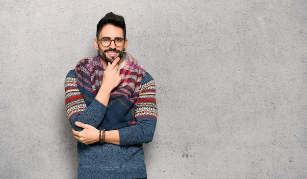 Hippie homme avec des lunettes et souriant sur un mur texturé