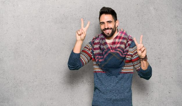 Hippie homme souriant et montrant le signe de la victoire avec les deux mains sur un mur texturé