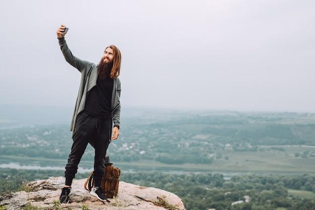 Un hipster attrayant avec une barbe se tient sur un rocher et fait un selfie.
