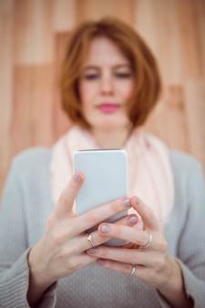 Hipster aux cheveux rouge à l'aide de smartphone