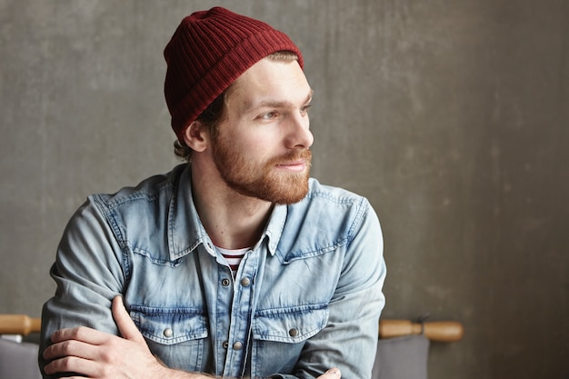 Hipster barbu d'apparence européenne portant une veste en jean et un chapeau élégant