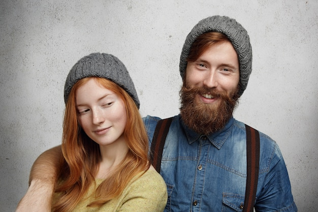 Hipster barbu gai en chemise en jean riant tout en serrant dans ses bras sa belle petite amie rousse qui le regarde avec un sourire mystérieux sournois.