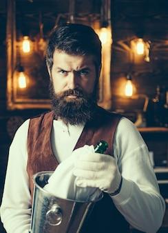 Le hipster barbu porte un gilet serviteur barbu brutal. barman hipster en gilet et gants