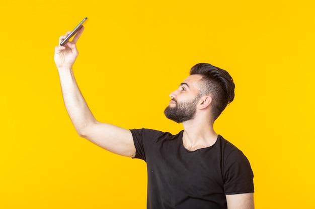 Hipster beau jeune homme barbu prenant un selfie sur son smartphone sur un mur jaune. concept