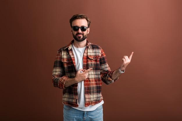 Hipster brutal bel homme barbu élégant sur brun