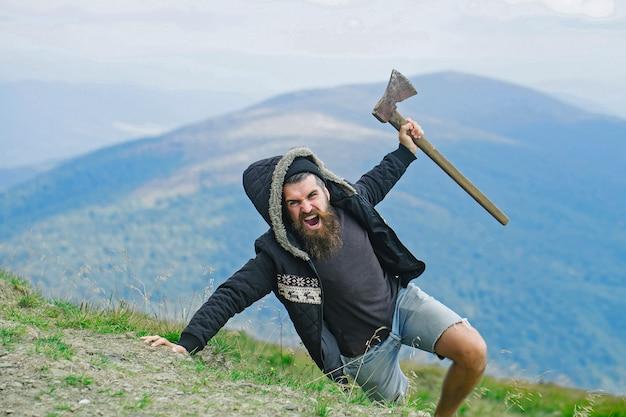 Hipster bûcheron avec longue barbe et moustache en manteau et capuche avec hache à la main sur la montagne sur ciel brumeux