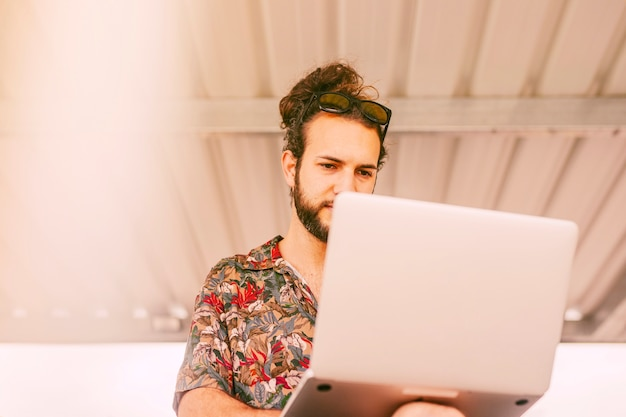 Hipster concentré travaillant sur un ordinateur portable à l'extérieur