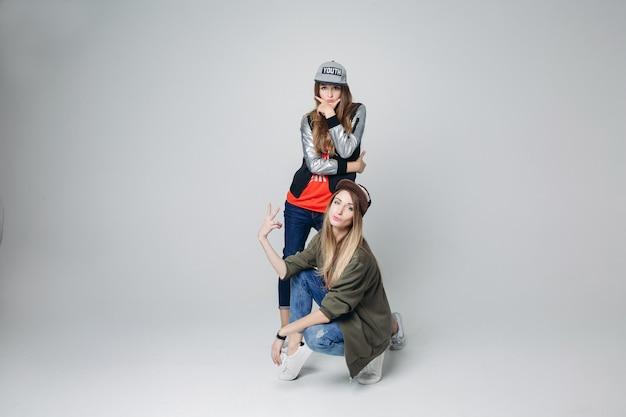 Hipster copines swag en vêtements élégants et casquettes sur la tête.