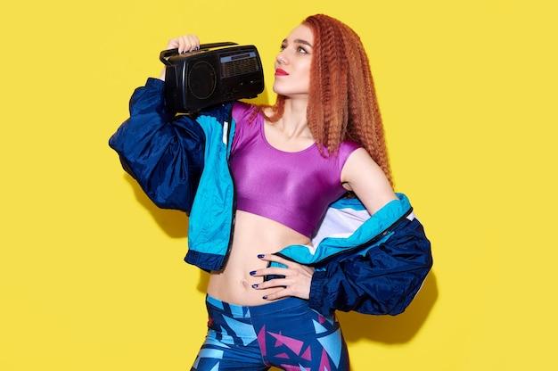 Hipster dj dame vêtue de vêtements lumineux détiennent une boîte de boom de bande rétro. concept de fan d'amateur de musique de temps de fête