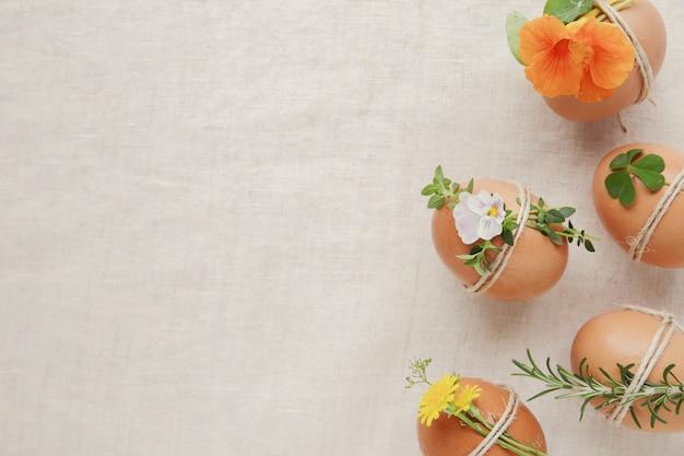 Hipster eco oeufs de pâques avec des fleurs et des herbes sur fond d'espace de copie de lin