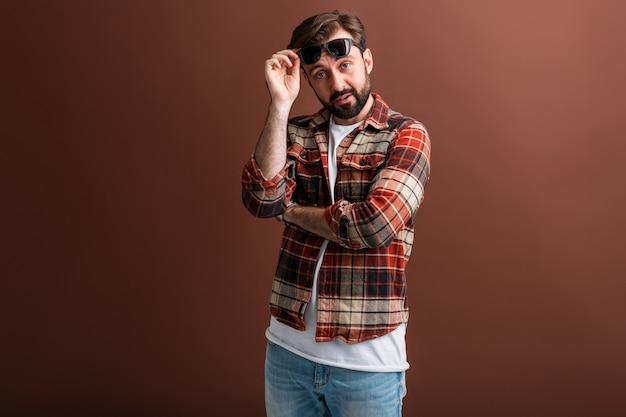 Hipster émotionnel bel homme barbu élégant sur brun