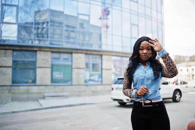Hipster fille afro-américaine portant une chemise en jean avec des manches léopard posant dans la rue contre un immeuble de bureaux moderne avec des fenêtres bleues et une voiture suv blanche.
