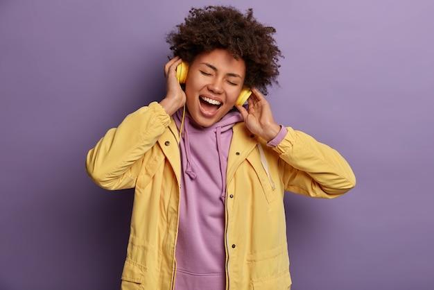 Hipster fille incline la tête, chante la chanson fort, bénéficie d'un son de bonne qualité dans les écouteurs, ferme les yeux, ne remarque personne