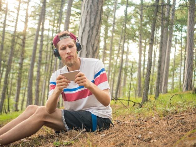 Hipster fou barbu en casual et cap assis dans la forêt avec téléphone et écouteurs jouant aux jeux sur smartphone