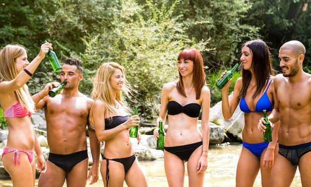Hipster friends millennials s'amuser ensemble à river lake excursion - concept d'amitié aventure avec de jeunes voyageurs buvant de la bière en bouteille à la fête d'été
