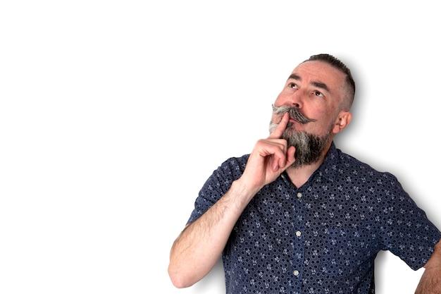 Hipster avec grande barbe et chemise sombre avec petite fleur à la recherche comme avoir des doutes en pensant