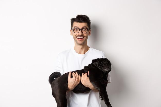Hipster heureux dans des verres tenant un mignon carlin noir et souriant, propriétaire de chien regardant la caméra avec un sourire étonné, debout sur fond blanc.