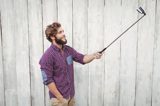 Hipster heureux en utilisant le bâton de selfie