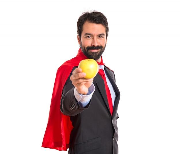Hipster homme d'affaires habillé comme un super-héros tenant une pomme